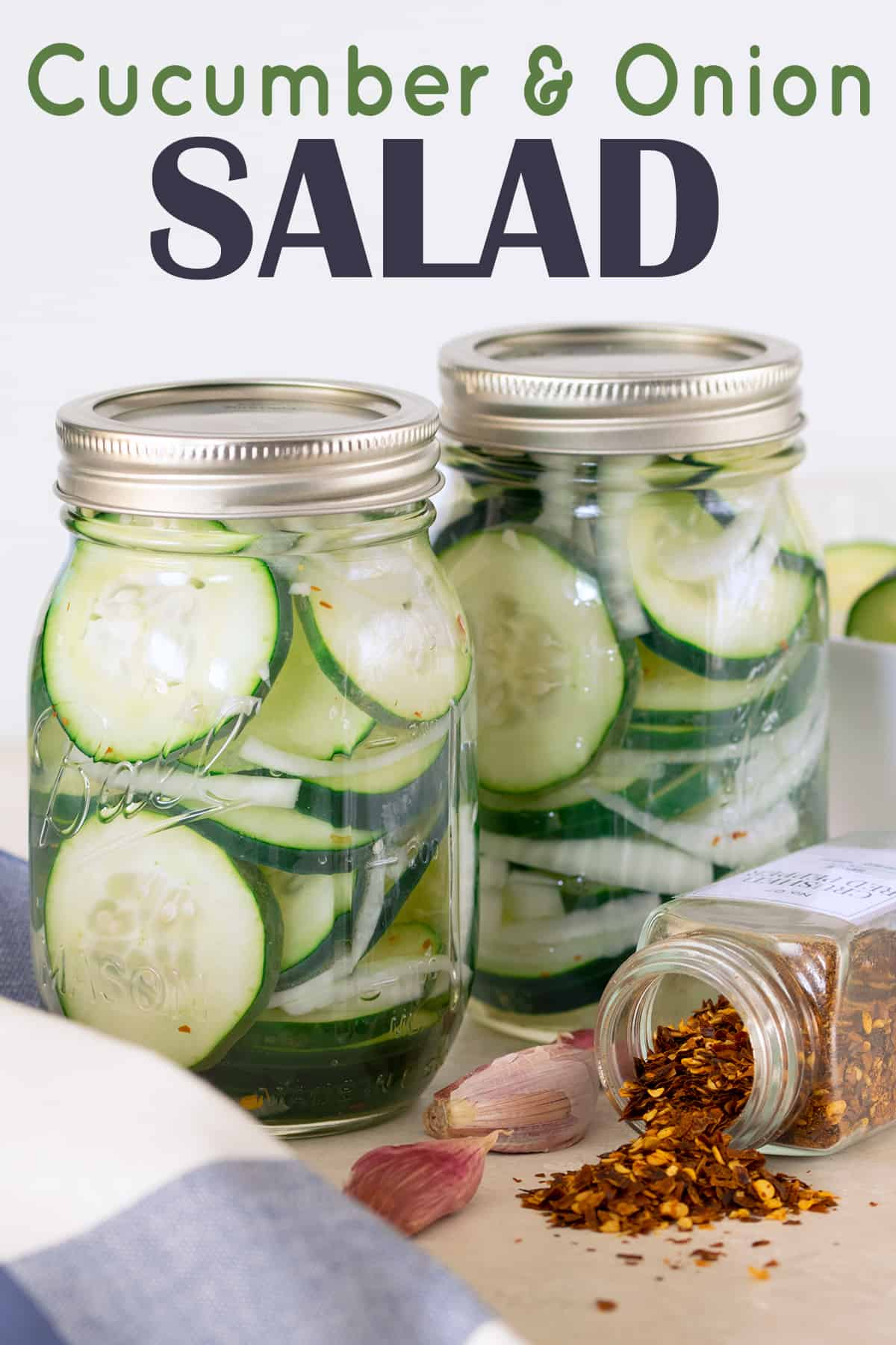 Two mason jars filled with cucumber and onion salad in vinegar on wooden table next to sliced cucumber.