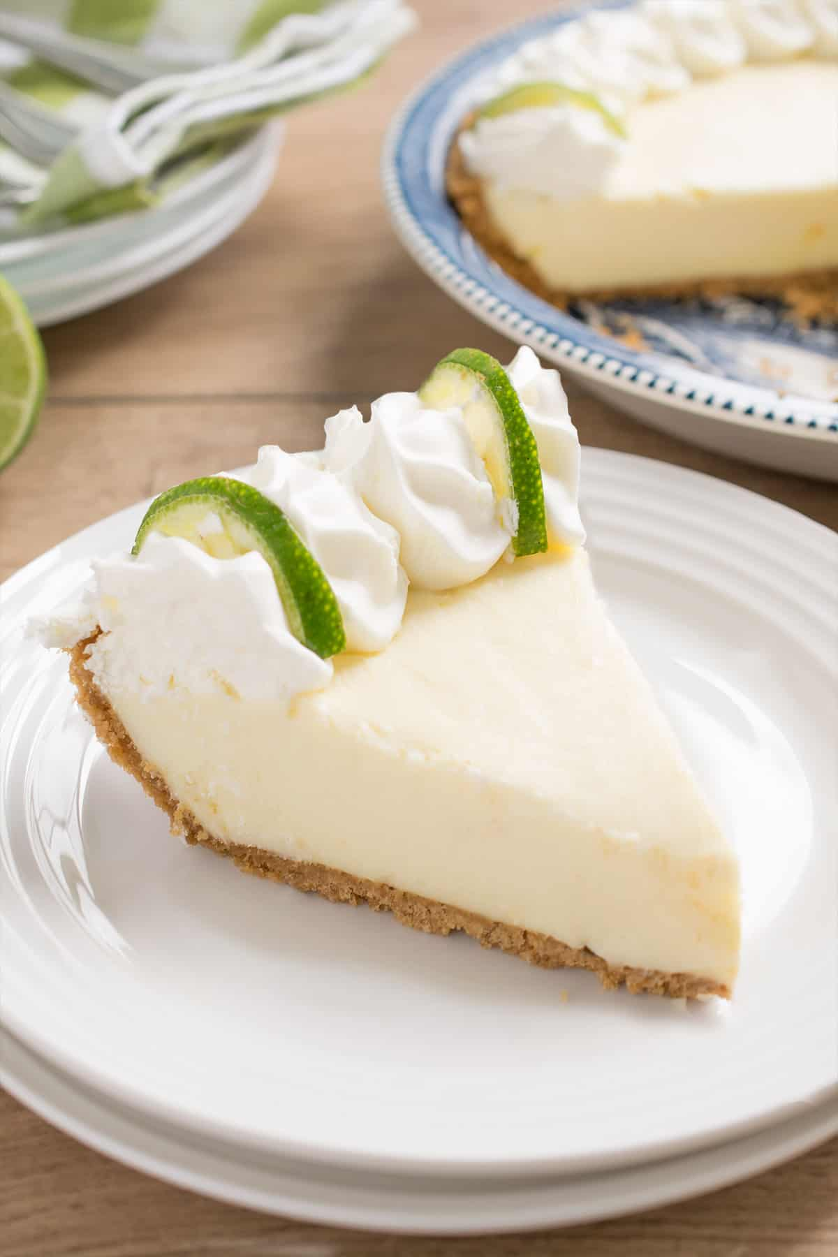 Key lime pie slice on stacked white plate with fresh whipped cream and lime slices.