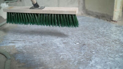 Push broom scrubbing garage floor.