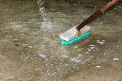 Cleaning floor with push broom.