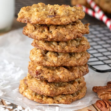 Coconut Pecan Cookies stacked seven high with shredded coconut and whole pecan scattered around.