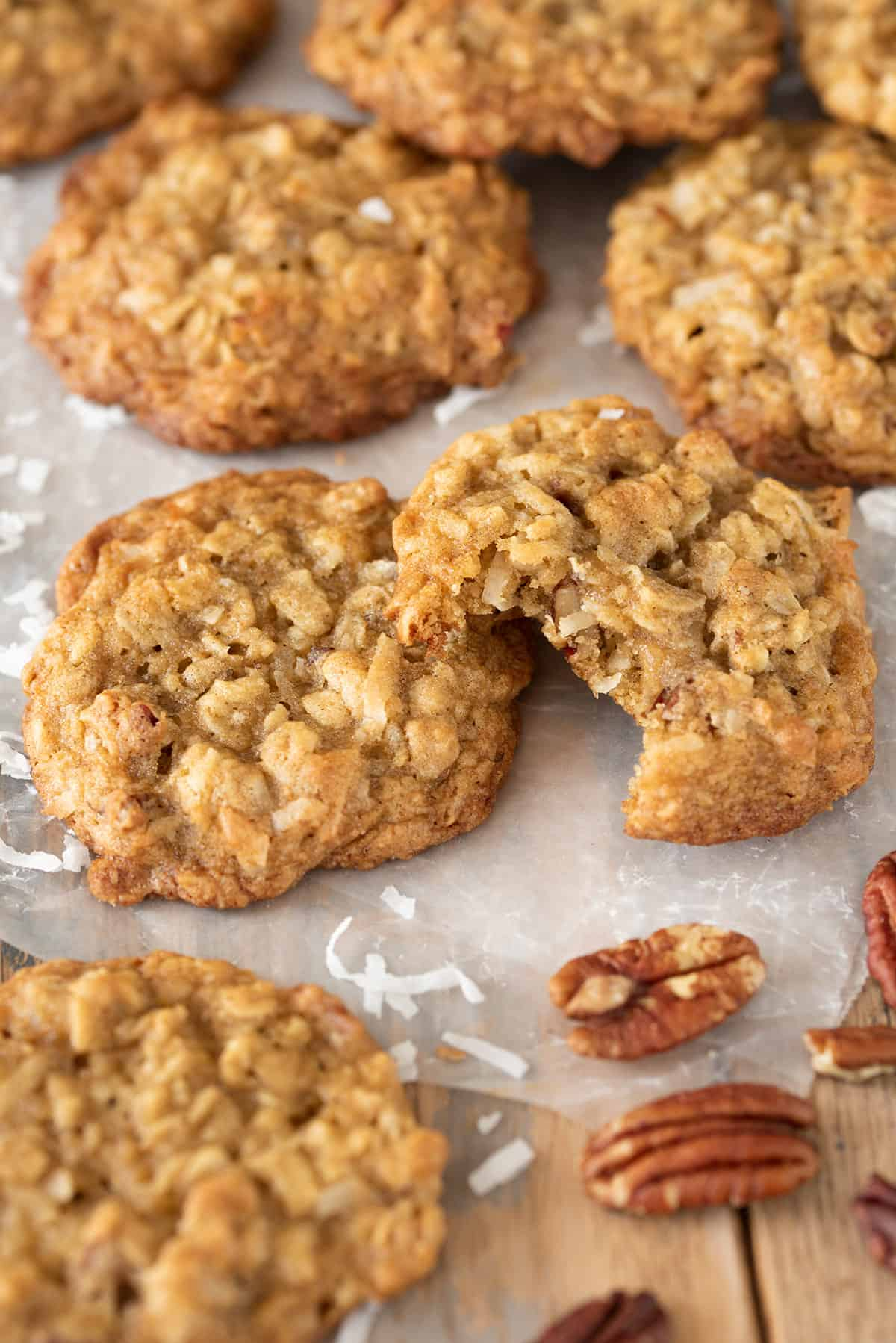 Coconut Pecan Cookies laid out on wax paper. One cookie has a bite taken out to show texture of the cookie.