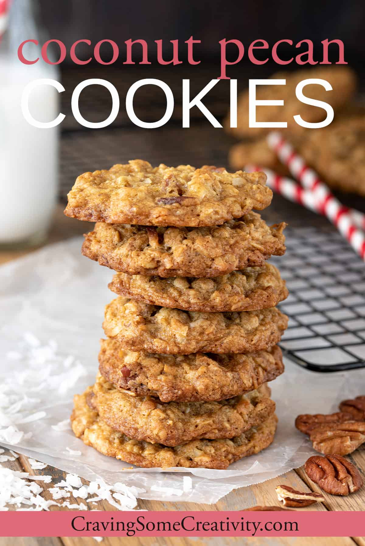 Coconut Pecan Cookies stacked in front with glass of milk and cookies in the background on a cookie sheet.