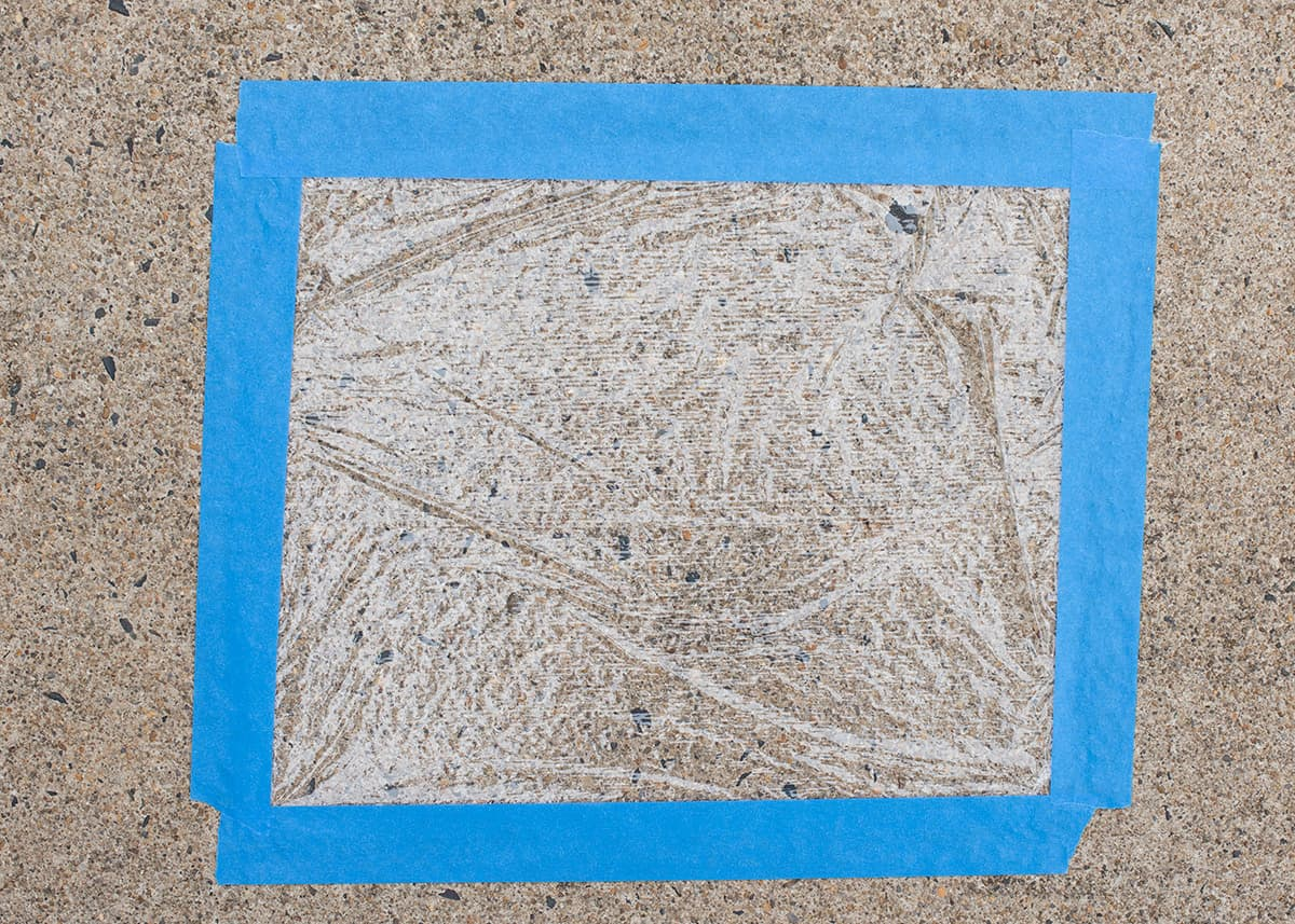 Concrete moisture test demonstration with plastic wrap and painter's tape on the floor.