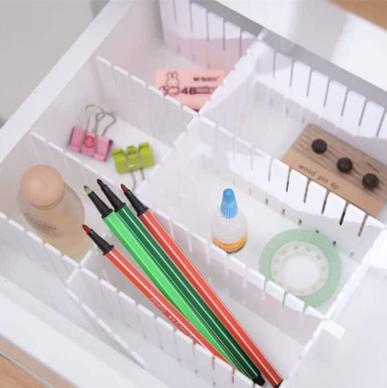 Top down view of drawer with plastic dividers and office tools in them.