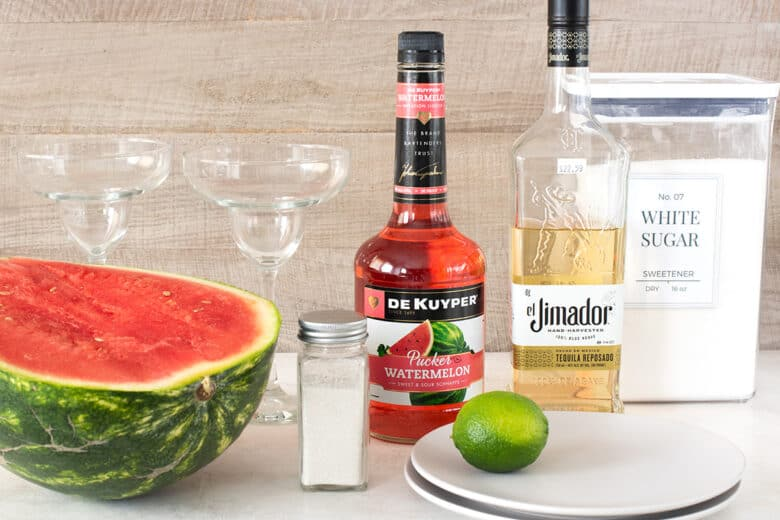 Watermelon Margarita ingredients laid out on a table including tequila, sugar, lime, watermelon, salt, and watermelon pucker.