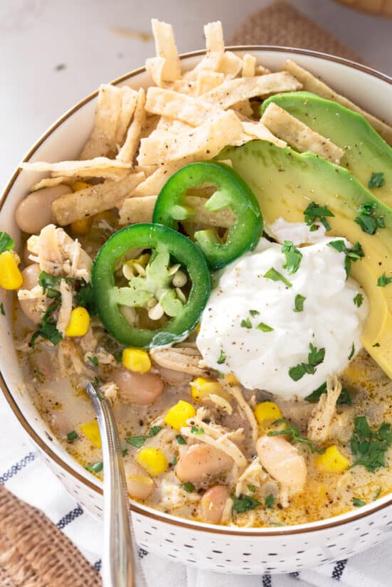 Top down view of a bowl of white chicken chili garnished with avocado, sour cream, jalapeno, and tortilla strips.