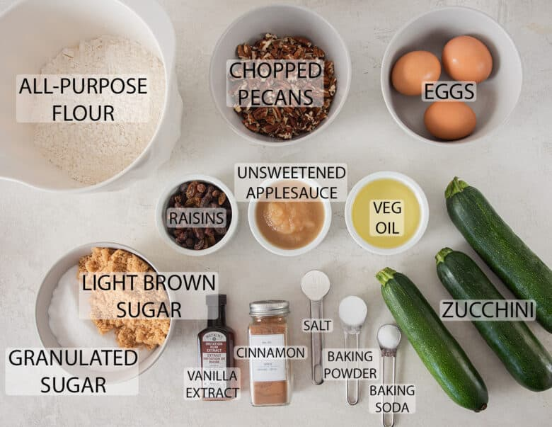 Ingredients to make zucchini muffins with raisins and pecans with text labels.
