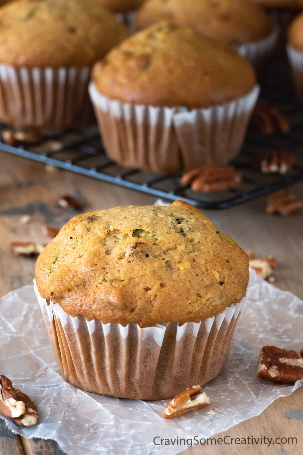 Zucchini muffin in wrapper centered on wood background with several other muffins in the background.
