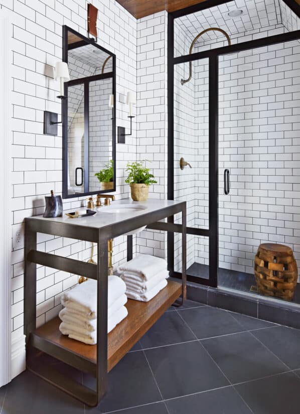 White tiled bathroom with black metal accents and black floor.