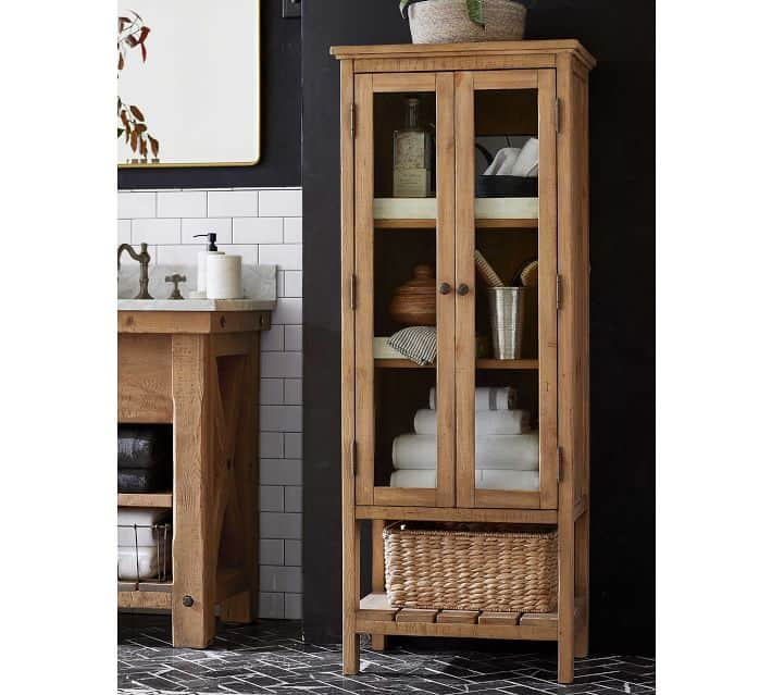 Rustic wood bathroom cabinet with glass doors in a black and white bathroom.