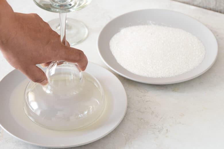 Demonstration of salt rimming a cocktail glass. A glass is dipped into a plate filled with lime juice while another plate is filled with kosher sea salt.