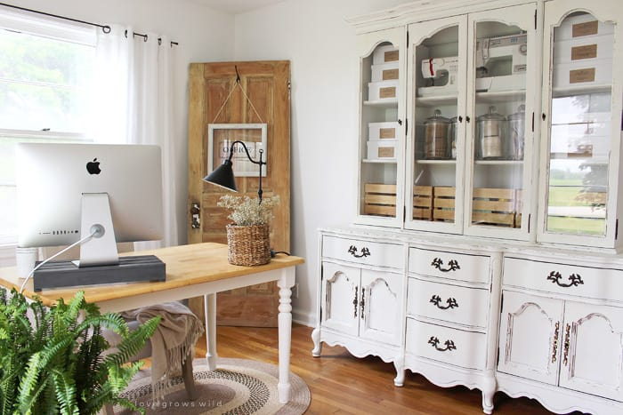 White farmhouse dining room with large display hutch that has craft supplies in it and glass jars.
