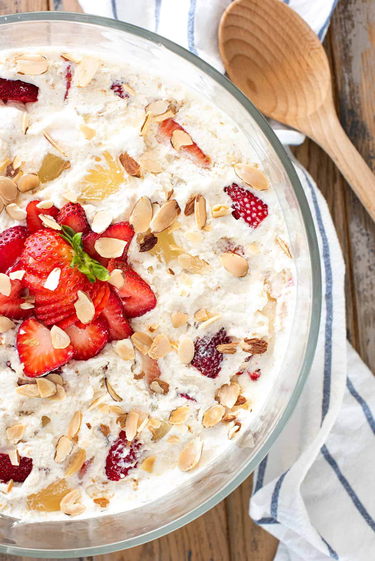 Punch Bowl Cake potluck dessert with whipped topping, nuts and strawberries in glass trifle bowl