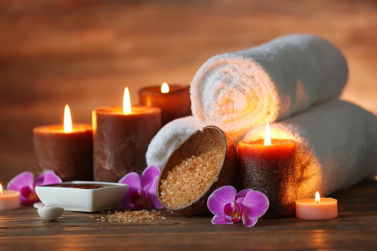 A grouping of spa products including lit candles, folded towels, salt scrub, and orchids on a wood background.