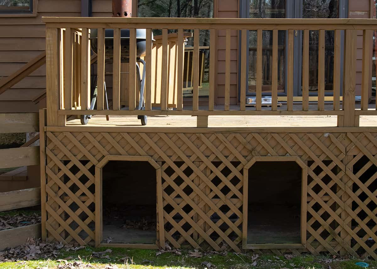 Wood stained deck with two cubbies cut out of lattice and framed for dog houses.
