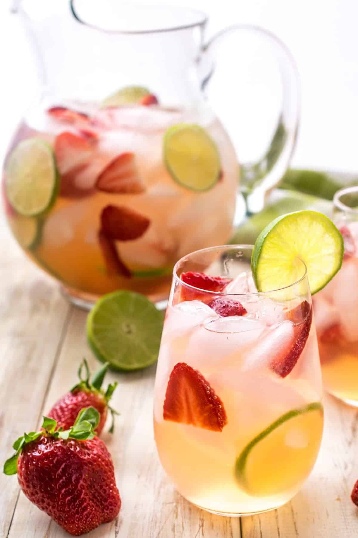 Strawberry sangria in a glass with lime garnish. Pitcher of strawberry sangria in the background. Whole strawberry and half lime on table top.