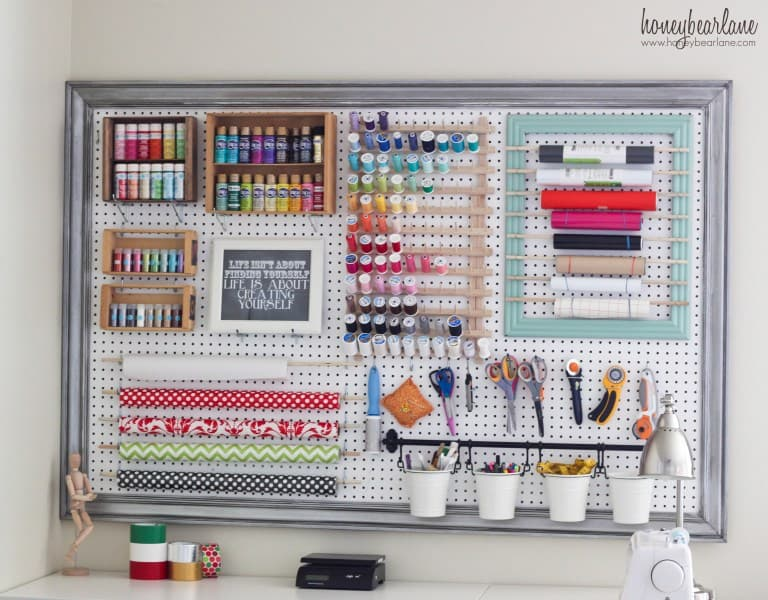 White pegboard on an office wall with craft supplies organized in it.