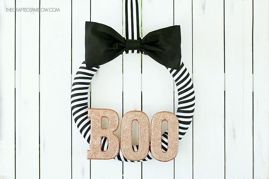 Black and white ribbon wreath with BOO in the center in metallic gold.