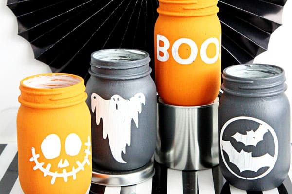 Mason jars painted with spooky characters on them in chalk paint.