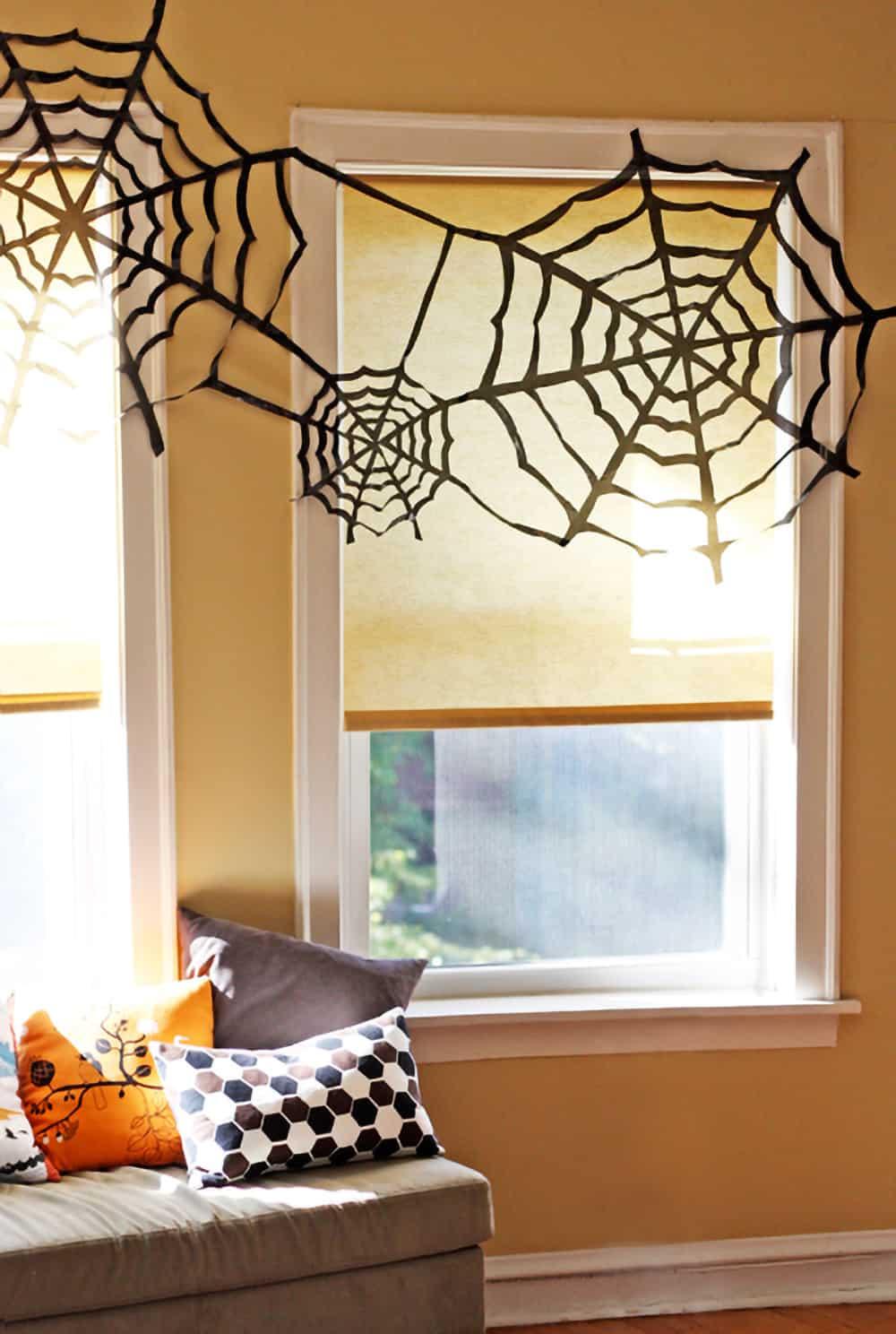 DIY trash bag spider webs as window decorations.