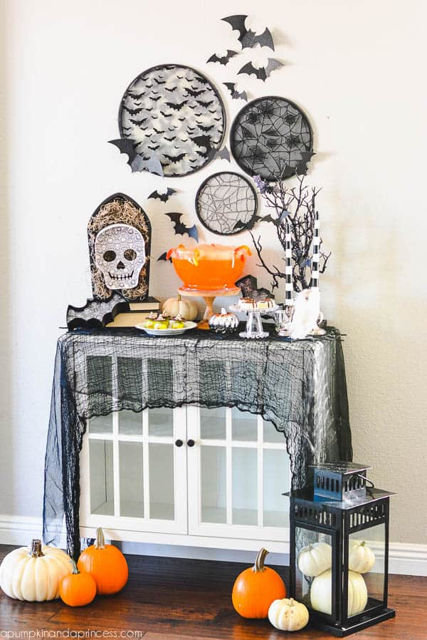 Halloween decorated buffet table with skulls, pumpkins, and a draped black scarf.