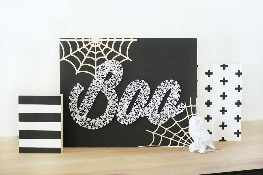 Small black sign that reads BOO and has string art spider webs on it.