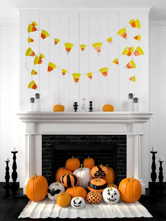 White mantle with candy corn banner and a pile of decorated pumpkins spilling out of the fireplace.