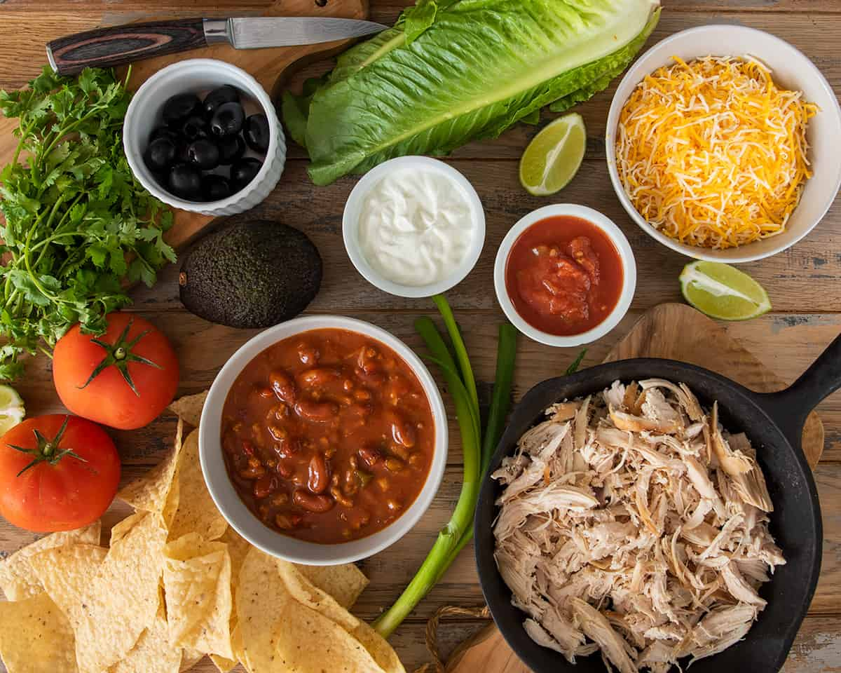 Layout of chicken chili nachos ingredients including salsa, sour cream, cheese, lettuce, tomato, olives, and avocado.
