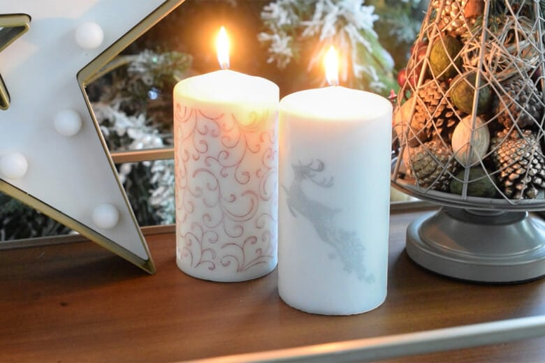 Two lit candles with stamped Christmas designs.