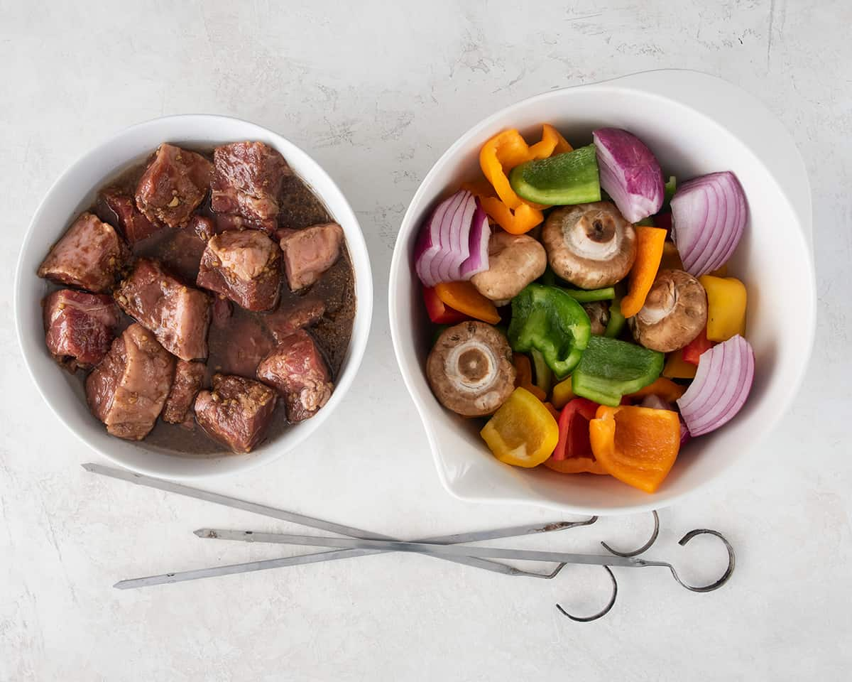 A bowl of marinated steak cubes and a bowl of cut vegetables with skewers laying below.