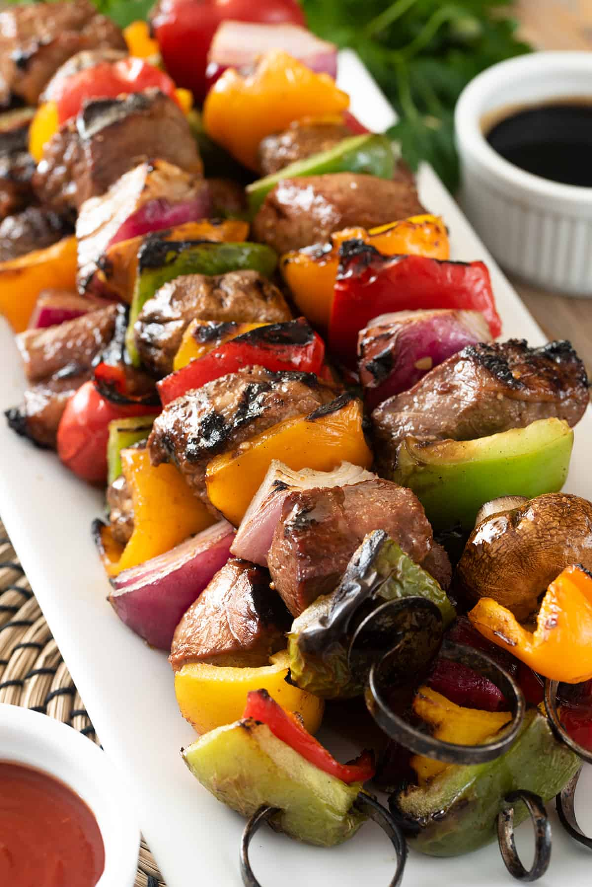 Side view of steak kabobs on metal skewers with peppers, mushrooms, and onions. Sauces on the side.