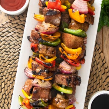 Skewered steak kabobs with peppers, mushrooms, and onions on a long serving platter.