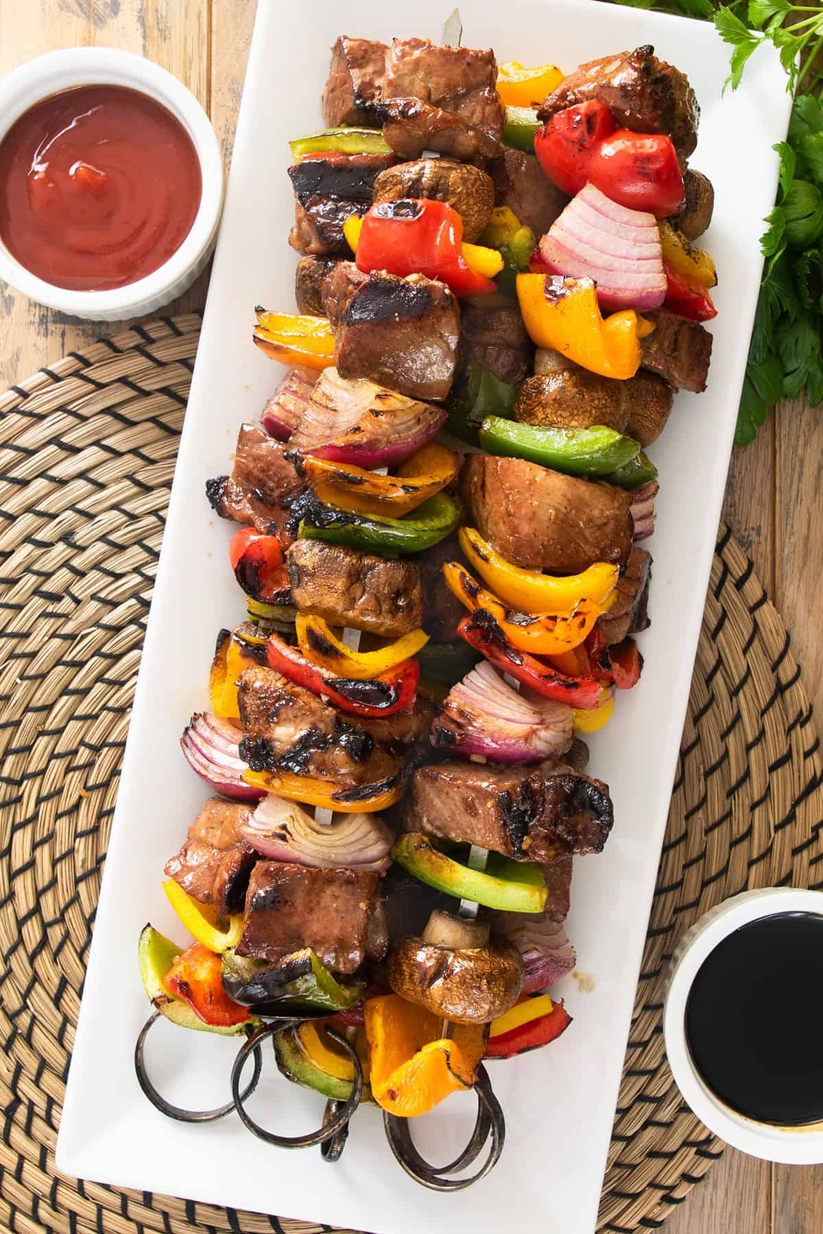 Steak kabobs on skewers with peppers, mushrooms, and onions. Sauces on the side.