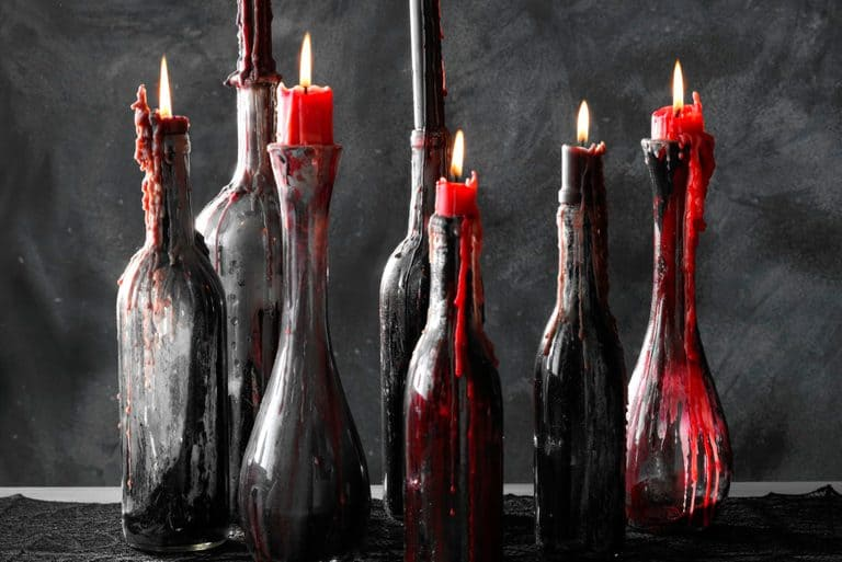 Wine bottles made with dripping candle wax in red and black.