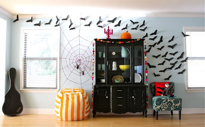 A black hutch with vinyl bats flowing overhead on a white wall and a spider web decoration.