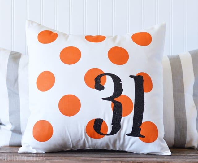 Throw pillow with orange polka dots and the number 31 designed on it.