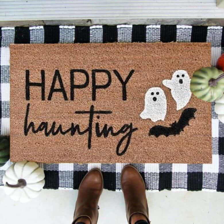 Happy Haunting Halloween doormat in front of door with buffalo check rug underneath.