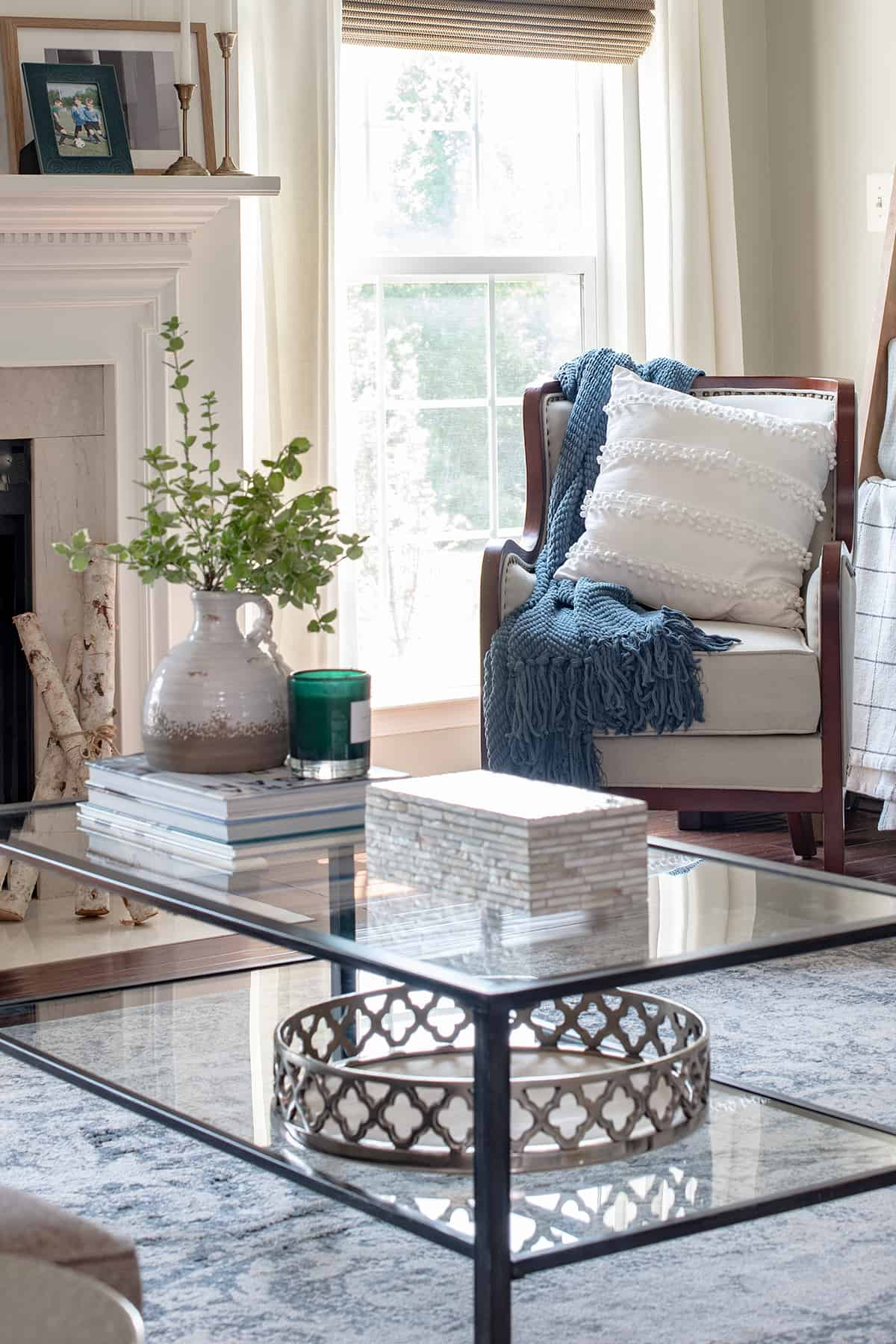 Coffee table with decor items and reading nook in front of a window.