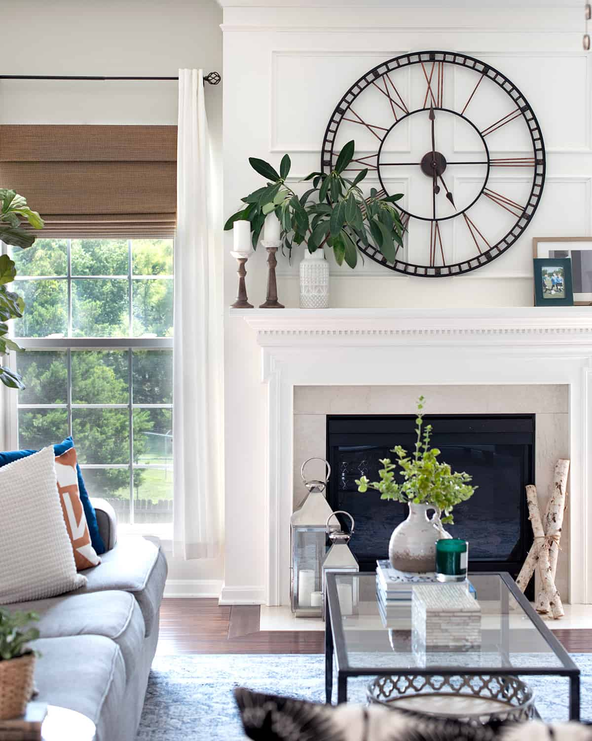 Neutral living room design with green accents and traditional fireplace style.