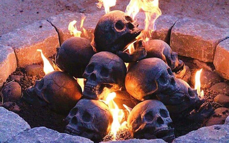 A pile of ceramic skulls in a firepit lit on fire.