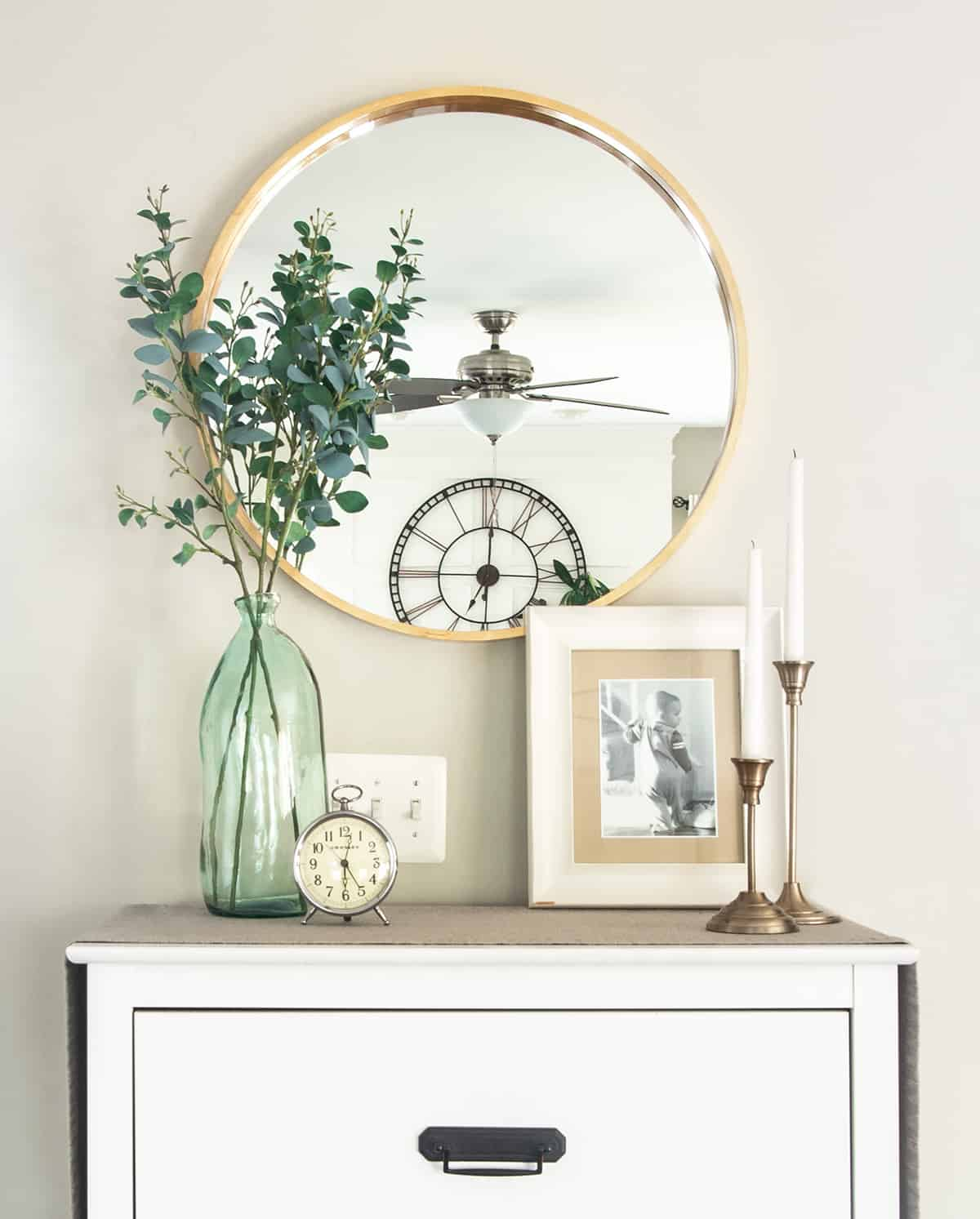 Small dresser decor items including a round mirror, vase, picture frame and candles.